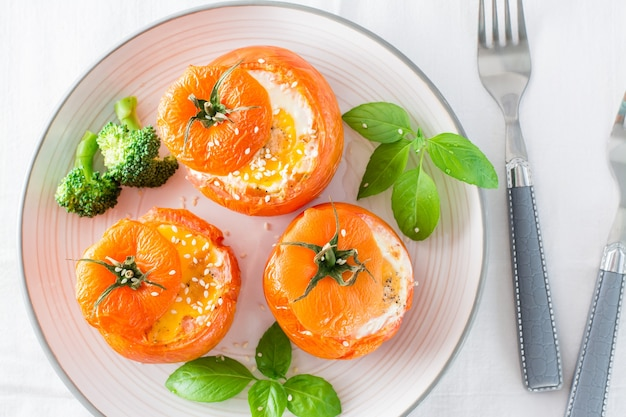 Tomates au four avec œuf, brocoli et feuilles de basilic sur une assiette. déjeuner diététique. vue de dessus