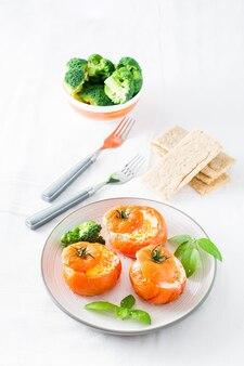 Tomates au four avec œuf, brocoli et feuilles de basilic sur une assiette. déjeuner diététique. vue verticale