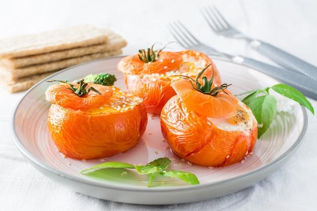 Tomates au four avec oeuf et feuilles de basilic sur la table. déjeuner diététique. fermer