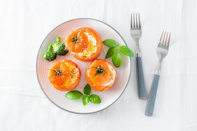 Tomates au four avec oeuf et feuilles de basilic sur la table. déjeuner diététique. vue de dessus