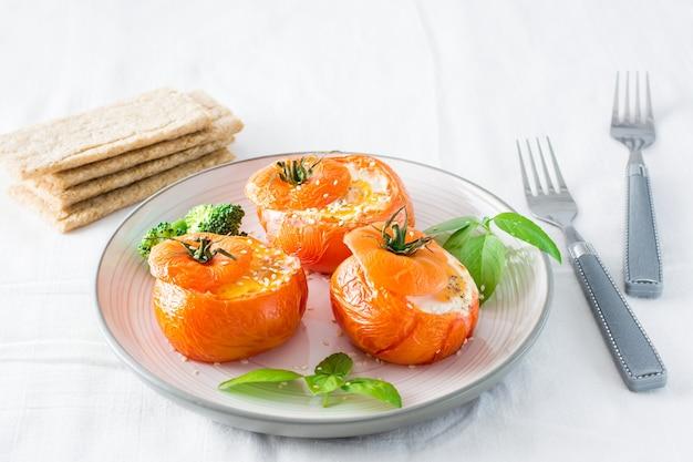 Tomates au four avec oeuf et feuilles de basilic sur la table. déjeuner diététique
