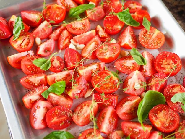 Tomates aux herbes provençales, basilic, thym et ail. ratatouille végétarienne d'aubergines, courgettes, tomates et sauce au poivron et tomate aux herbes en céramique avant la cuisson. vue de dessus.