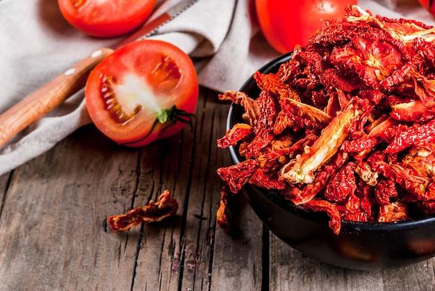 Tomates bio séchées au soleil maison croustilles de tomates croustillantes sur une vieille table en bois rustique avec des tomates fraîches et de l'huile d'olive