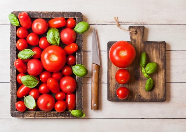 Tomates biologiques au basilic dans une boîte en bois vintage sur une table de cuisine en bois