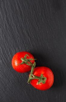 Tomates biologiques de concept alimentaire sur ardoise noire avec espace de copie