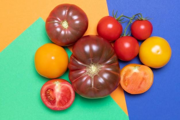 Tomates biologiques de différentes couleurs sur fond vert, orange et bleu