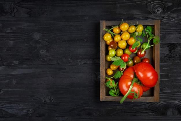 Tomates biologiques de différentes variétés et couleurs dans une boîte en bois et texture noire