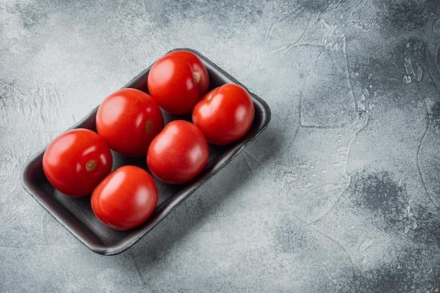 Tomates biologiques rouges fraîches, sur fond gris avec espace de copie pour le texte
