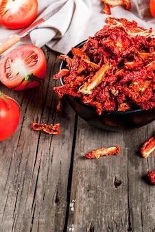 Tomates biologiques séchées au soleil maison, chips de tomates croustillantes, sur une vieille table en bois rustique avec des tomates fraîches et de l'huile d'olive. fond