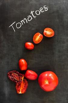 Tomates biologiques séchées et fraîches sur tableau noir par dessus tableau noir