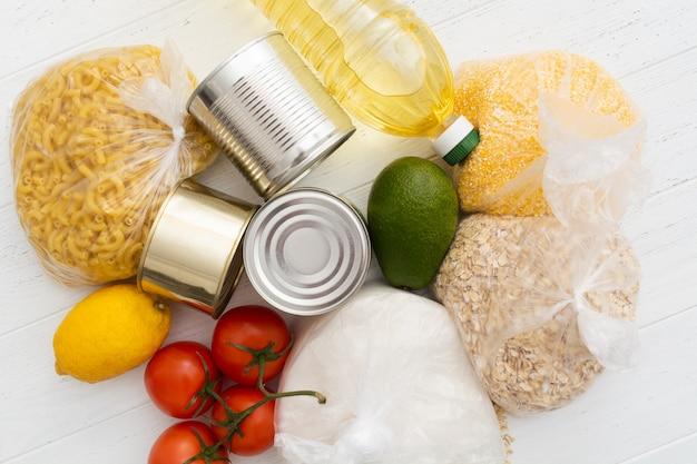Tomates, boîtes de conserve, avocats et plus de nourriture sur une table en bois blanc
