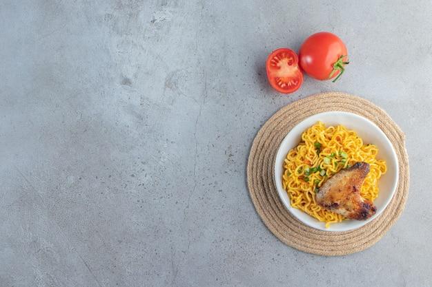Tomates et bol de nouilles sur un dessous de plat, sur le fond de marbre.