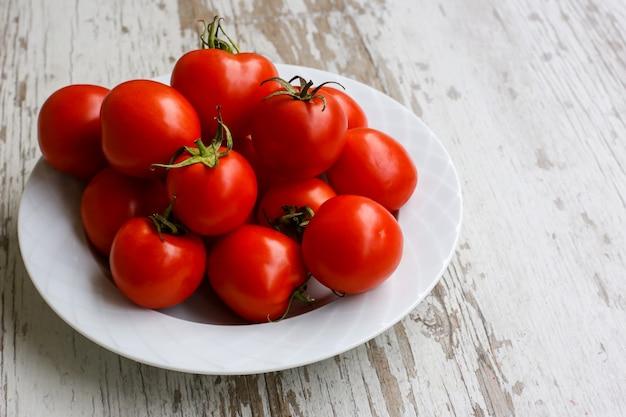 Tomates brillantes et saines sur une plaque blanche