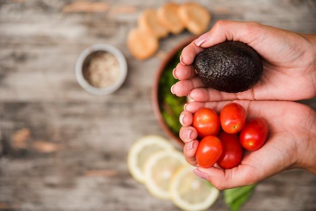 Tomates cerises et avocat dans les mains sur un bureau en bois flou