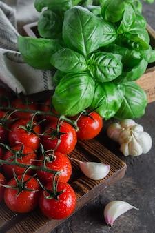 Tomates cerises biologiques au basilic et à l'ail sur une planche à découper