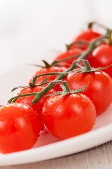 Tomates cerises sur une branche dans une assiette