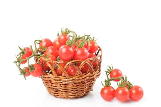Tomates cerises sur des brindilles dans un panier isolé sur fond blanc