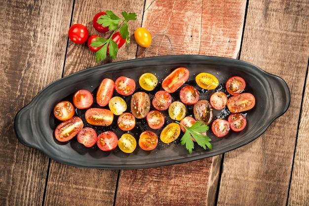 Tomates cerises colorées tranchées avec de l'huile et des épices, vue de dessus
