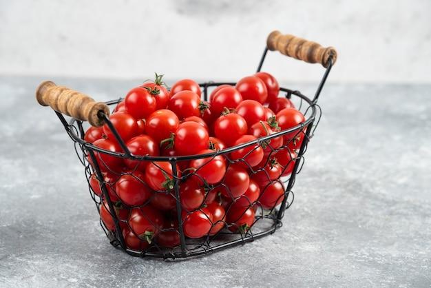 Tomates cerises dans un panier métallique sur table en marbre.