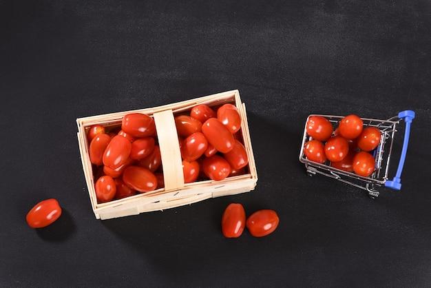 Tomates cerises dans un panier en osier et vue de dessus du panier