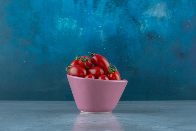 Tomates cerises dans une tasse sur bleu.