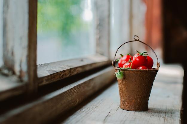 Tomates cerises dans un vieux seau décoratif rouillé sur un rustique foncé.