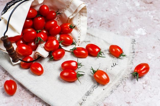 Tomates cerises de différentes couleurs, tomates cerises jaunes et rouges sur fond clair