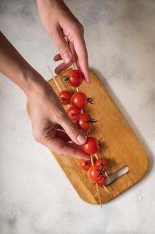 Tomates cerises sur des épées dans les mains, le processus de cuisson. vue d'en-haut.