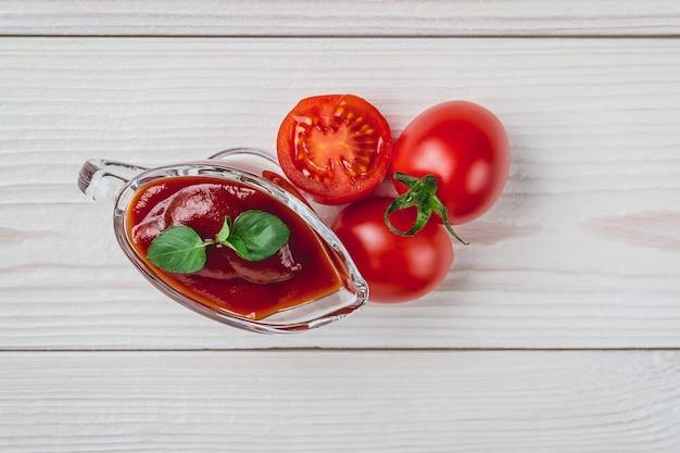 Tomates cerises, épices et une saucière en verre avec du ketchup sur une surface blanche