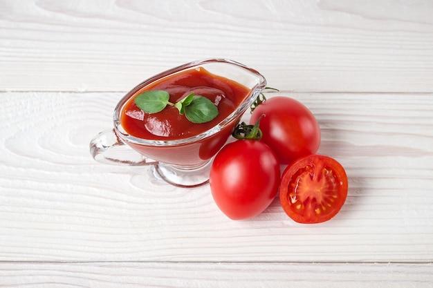 Tomates cerises, épices et saucière en verre avec du ketchup.