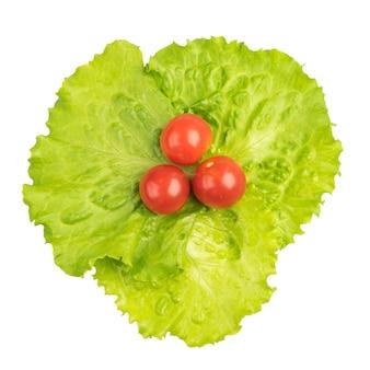 Tomates cerises sur feuille de salade verte isolée