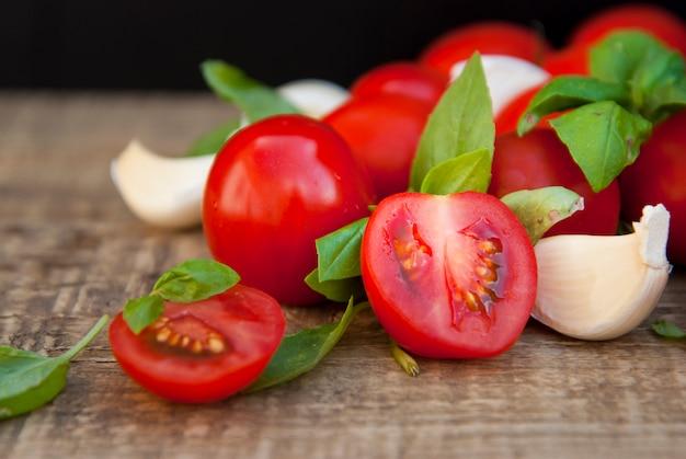 Tomates cerises avec feuilles de basilic et ail.