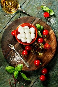 Tomates cerises, feuilles de basilic, fromage mozzarella et huile d'olive f