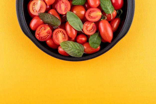 Tomates cerises et feuilles de menthe dans un bol noir sur la surface jaune vue de dessus avec copie espace