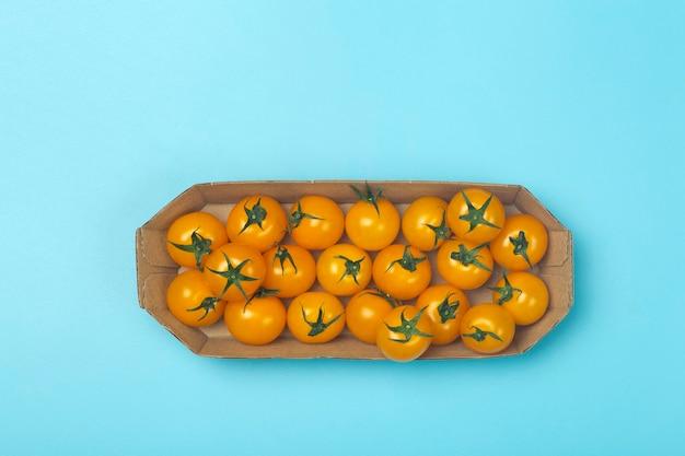 Tomates cerises sur fond bleu coloré.
