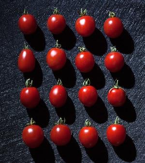 Tomates cerises sur fond noir disposées de manière linéaire.