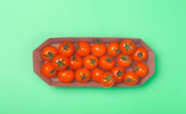 Tomates cerises sur fond vert coloré.