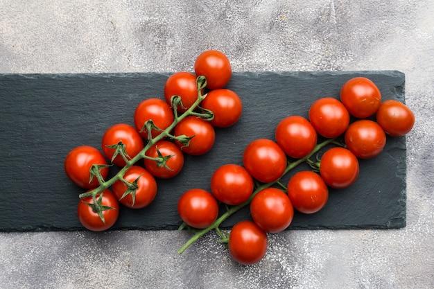 Tomates cerises fraîches sur une branche sur un fond de béton noir.
