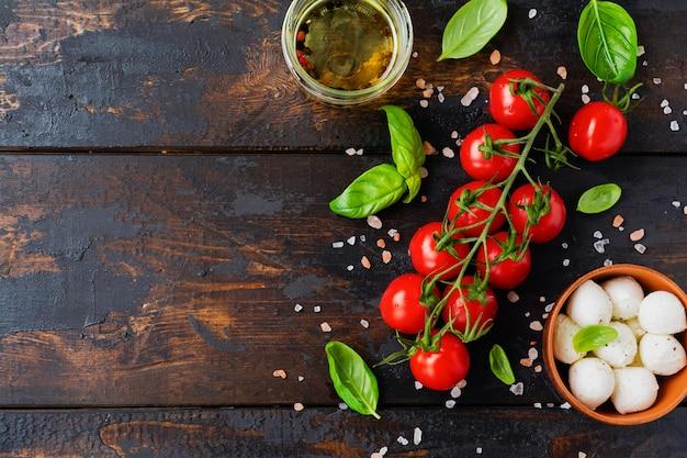 Tomates cerises fraîches, feuilles de basilic, fromage mozzarella et huile d'olive sur fond de bois ancien. ingrédients de la salade caprese. mise au point sélective.