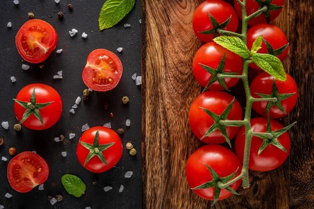 Tomates cerises fraîches sur fond noir avec des épices.