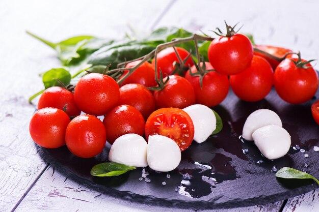 Tomates cerises fraîches, mozzarella et épinards verts sur fond en bois.