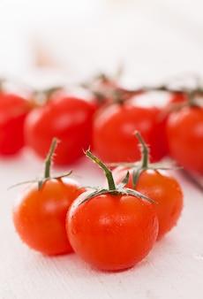 Tomates cerises fraîches sur une surface blanche