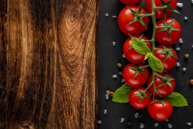 Tomates cerises fraîches sur un tableau noir avec des épices