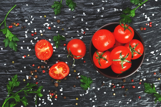 Tomates cerises fraîches en tranches avec épices gros sel et fines herbes