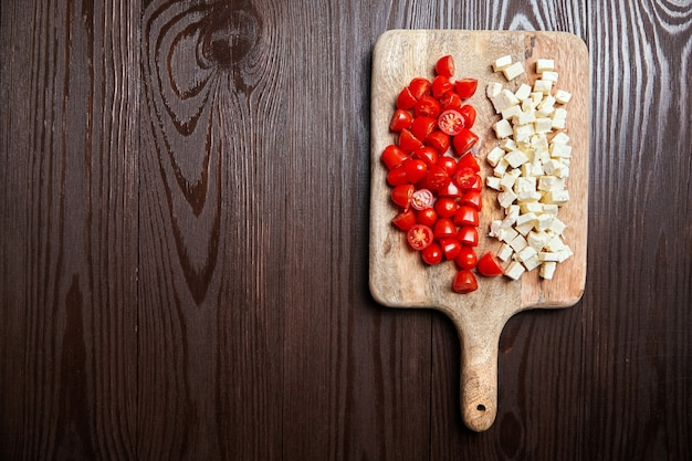 Tomates cerises avec fromage à salade sur une planche à découper sur fond de bois avec copie espace, vue de dessus