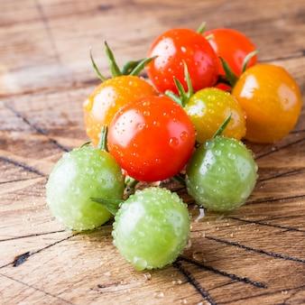 Tomates cerises en gouttes sur une table en bois. une branche de tomate multicolore verte, jaune et rouge