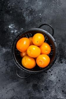 Tomates cerises jaunes dans une passoire