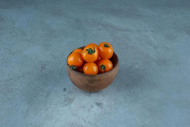 Tomates cerises jaunes dans une tasse sur bleu.