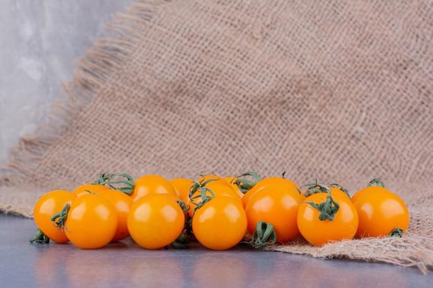 Tomates cerises jaunes isolées sur une surface bleue