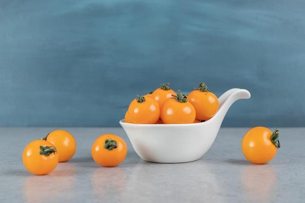 Tomates cerises jaunes isolés sur une table en béton gris.